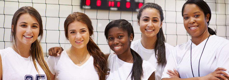 Female volleyball players and their coach
