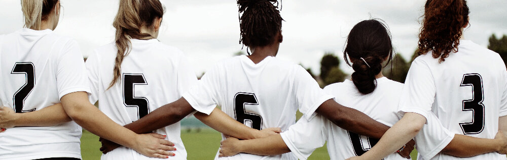 Female soccer players arm in arm